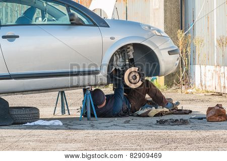 Male Mechanic Working under Car