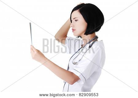 Worried female doctor analysing x-ray image.