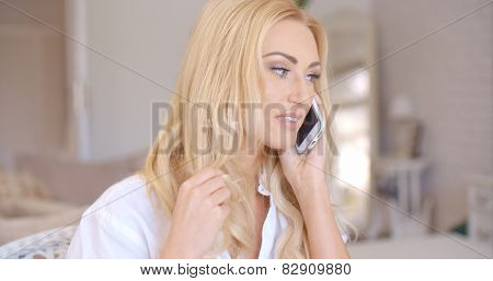 Close up Smiling Young Female Talking through Phone While Touching her Blond Hair