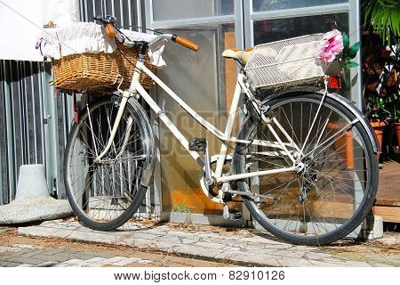 Bicycle With Wicker Basket Stands Near Wall
