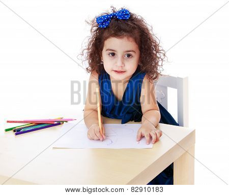 charming curly little girl draws with markers while sitting at t