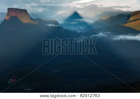 Shadow of the conical mountain Adam's Peak - sacred buddhist place. Sri Lanka