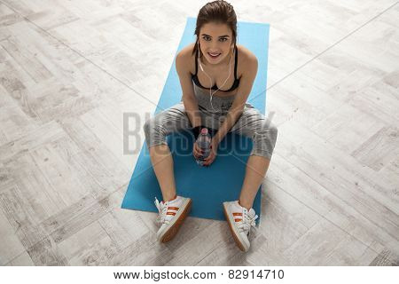 Happy sports woman sitting on the yoga mat and holding bottle of water