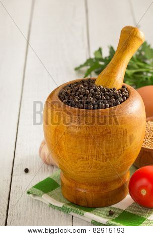 mortar with pestle and spices on wooden background