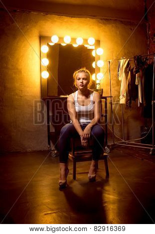 Blonde Woman Posing On Chair At Dressing Room In Theater