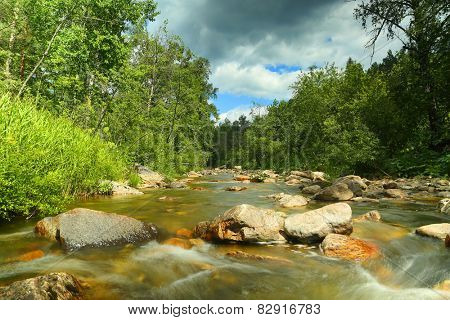 landscape with mountain river flowing over rocks at summer - long exposure