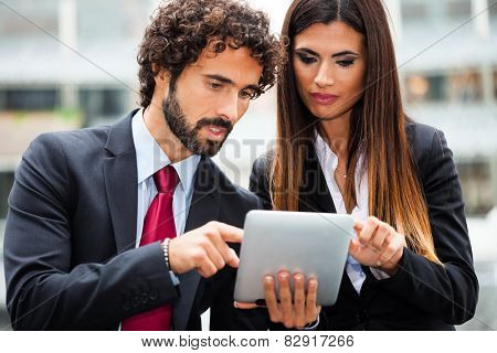 Two business people using a digital tablet