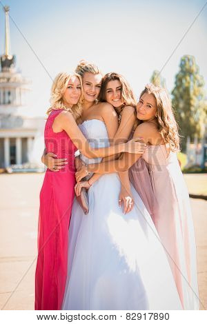 Beautiful Bride Hugging With Bridesmaids At Sunny Day