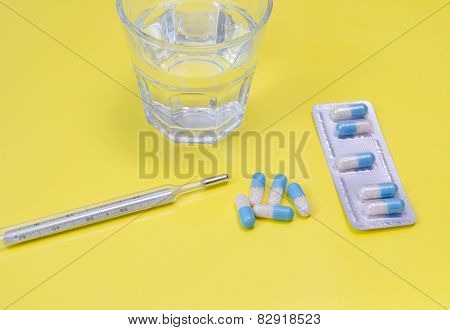 Water Glass,  Thermometer And Medicaments On Yellow
