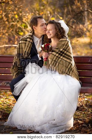 Newlyweds Kissing On Bench At Autumn Park Under Woolen Plaid