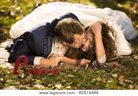 Young Groom Kissing Beautiful Bride In Cheek Lying On Grass At Park
