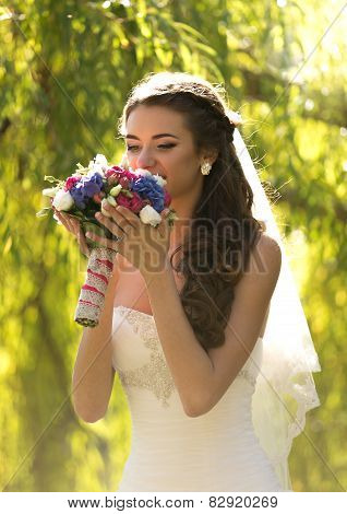 Portrait Of Elegant Brunette Bride Smelling Wedding Bouquet