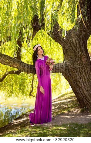 Sexy Woman In Long Dress Leaning Against Big Tree At Riverbank