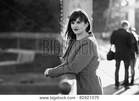 Black And White Portrait Of Woman Standing On Bridge At Windy Day