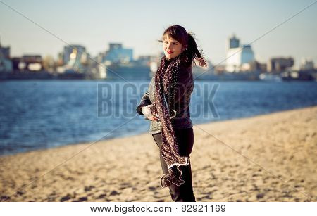 Young Woman Standing On Beach At Windy Autumn Day