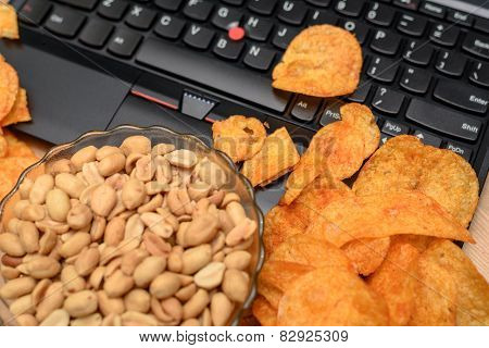 Close Up Of Open Laptop With Chips Scattered On Keyboard And Bowl Of Peanuts