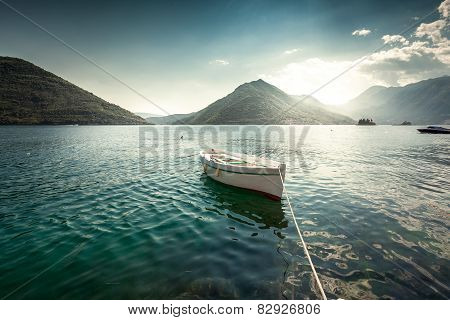 White Rowboat Moored At Bay Surrounded By Mountains