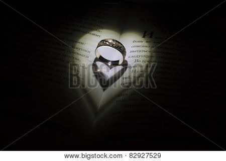 Golden ring with heartshadows in the middle of the book