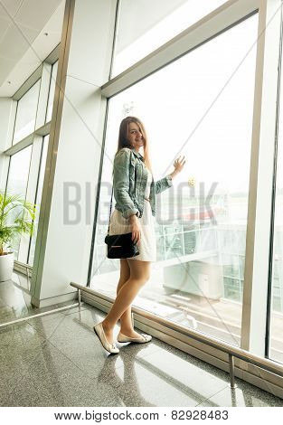 Young Woman Looking At Window At Modern Airport Terminal