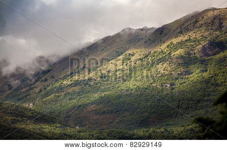 Landscape Of High Mountains Grown With Grass Covered With Clouds