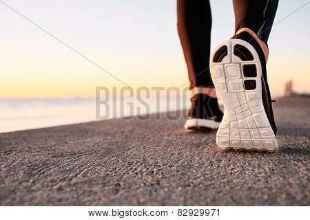 Runner man feet running on street closeup on shoe. Male wellness competitor jogger workout in health