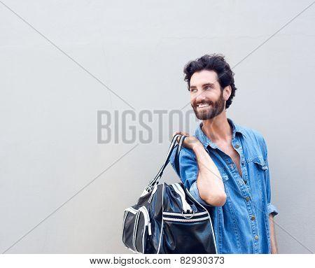 Smiling Man Holding Travel Bag And Looking Over Shoulder