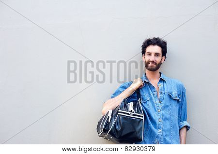 Young Man Standing With Travel Bag Over Shoulder