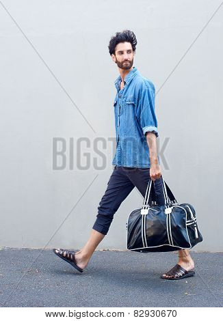 Side View Portrait Of A Young Man Walking With Travel Bag