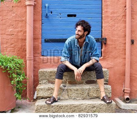Cool Fashionable Young Man Sitting Outdoors On Door Step