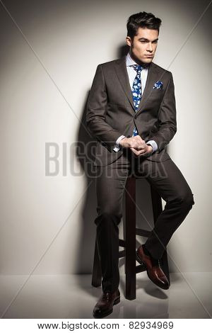 Full body picture of a young business man sitting on a stool while looking down thinking.