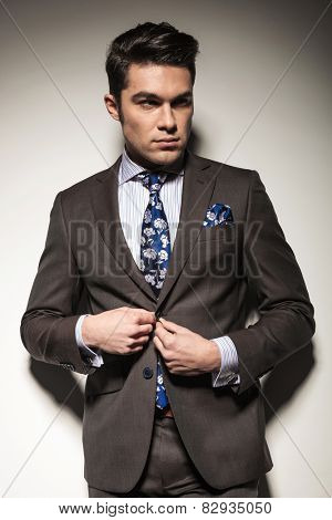 Handsome business man looking away from the camera while closing his jacket, on studiobackground.