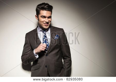 Happy business man smiling away from the camera while holding his fist up. On grey studio background.