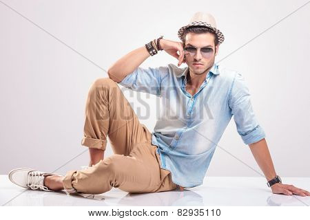 Young casual man sitting on the floor leaning his hand on his knee, looking at the camera