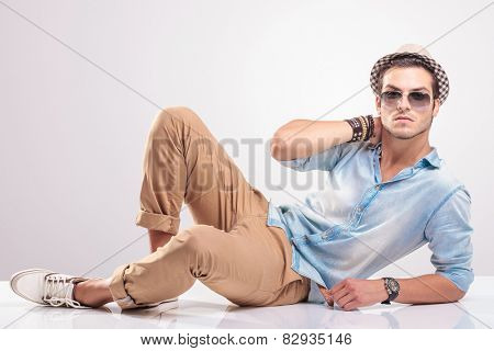 Young fashion man holding his hand to his neck while lying on the floor.