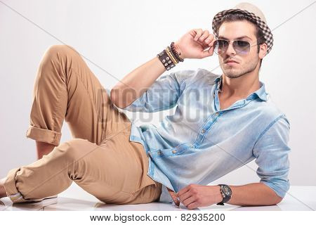 Attractive young man lying on studio background while taking off his sunglasses.