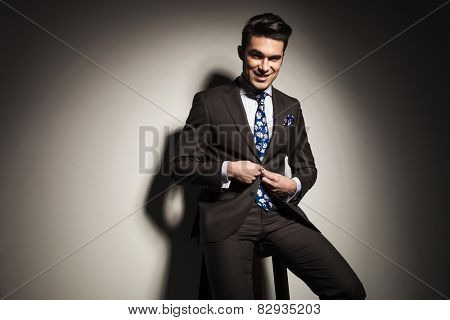 Smiling business man sitting on a stool while closing his jacket. Against grey studio background.