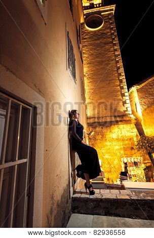 Night Shot Of Woman Leaning Against Old Building At Street