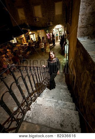 Night Shot Of Woman In Dress Walking Up The Stairway On Street