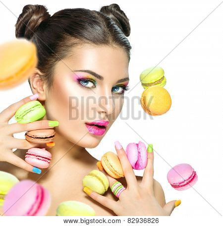 Beauty fashion model girl with colourful makeup and manicure taking colorful macaroons. Beautiful woman, bright make-up. Purple lipstick, vivid eyeshadow and accessories.Diet,dieting concept. Sweets.