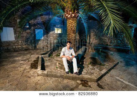 Elegant Man Sitting Under Big Palm On Street At Night