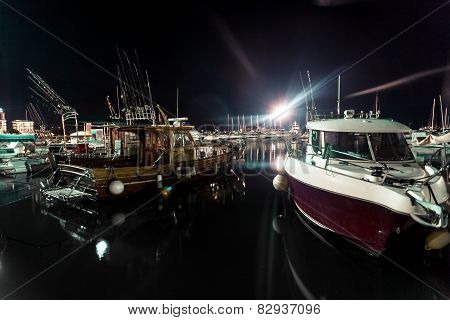 Night Shot Of Wooden And Motorboats Moored At Sea Port