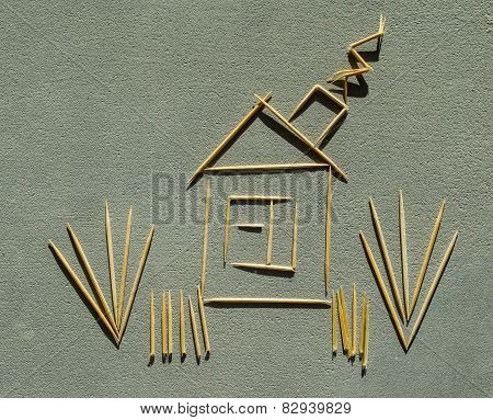 House, smoke and grass made of toothpicks on concrete