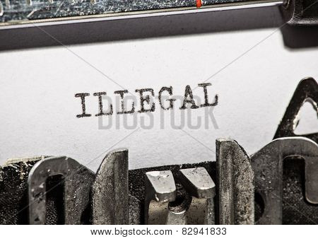 Typewriter with white paper page on wooden table. sample text Illegal.