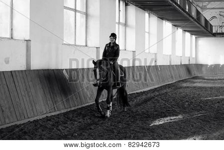 Black And White Photo Of Woman Riding Horse At Indoor Manege