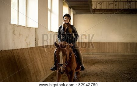Woman Riding Beautiful Brown Horse At Indoor Manege