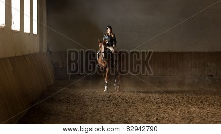 Young Woman Jockey Doing Training At Riding Hall