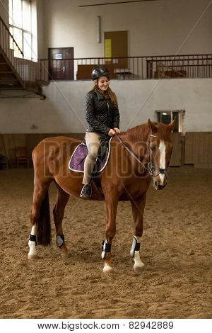 Young Woman Riding Brown Horse In Indoor Manege