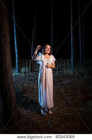 Young Woman In Nightgown Walking In Forest At Night With Gas Lamp