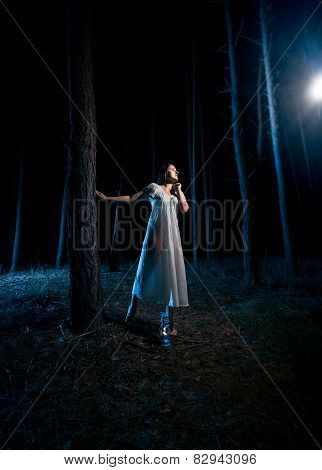 Woman In White Nightgown Looking At Beam Of Light At Night Forest