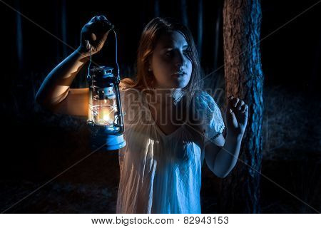 Portrait Of Scared Woman Lost In Forest Lighting Up The Way With Lantern